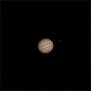 Jupiter, moon Io, and Io's shadow on the surface of Jupiter