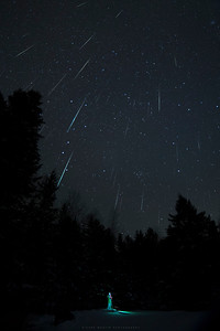 "This ia another composite of the Geminids taken with my Canon 6D and a Rokinon 14mm lens at f2.8. Late at night, with Gemini crossing the zenith, and meteors seen ""falling"" straight down in every direction. This image contains 49 Geminids, digitally stacked in Photoshop. Taken on the morning of December 14 2017.  What is that down on the ground?! Alien? Christmas Tree? No, it's Shane who just happened to stand out there with his camera, taking pictures. This is one of those unplanned shots, as I had no idea he was going to stand there and be lit up perfectly with his head lamp. It turns out that I like the result"