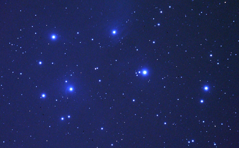 Messier M45 Pleiades, Seven Sisters, Subaru or Matariki - 31/10/2010 (Processed JPEG Stack)<br /> <br /> One of the most well known of open clusters, the Pleiades or Seven Sisters, located in Taurus at ~400 Light Years distance is amongst the nearest star clusters to Earth. It is the most obious cluster to the naked eye. It has been named in many ancient cultures. The cluster is dominated by hot blue and extremely luminous stars that have formed within the last 100 million years. Dust that forms a faint reflection nebulosity around the brightest stars was thought at first to be left over from the formation of the cluster, but is now known to be an unrelated dust cloud in the interstellar medium that the stars are currently passing through.<br /> <br /> First 'stacked' and guided image of this extended field object. 5 images stacked using DeepSkyStacker 3.3.2 and cropped and colour adjusted by GIMP. Taken through the Apogee 80 on the SkyWatcher NEQ6 mount. Guided for 180sec @ISO 400 in-camera JPEG with no in-camera dark, no field flattener but with a light pollution filter. I took a single dark frame, but as a JPEG, and discovered afterward that darks must be RAW images, not compressed.<br /> <br /> Things to note is the excessive blue processing and that the nebulosity is very tenuous and over-processed to have it show clearly. Hot pixel removal in DSS without dark processing leaves several black spots around the image. This is however a big improvement over my first single JPEG image on 26/09/2010.<br />  <br /> Limited cropping is possible due to the size of this object so some spherical aberration is evident near the outer edges of the image. Focused using a Bahtinov Mask. <br /> <br /> Telescope - Apogee OrthoStar LOMO 80/480 without Field Flattener, Hutech LPS-P2 light polution filter, Canon 400D DSLR, Ambient xxC not noted. Mount - Skywatcher NEQ6 Pro. Guidescope - Orion ShortTube 80 with Star Shoot Auto Guider.