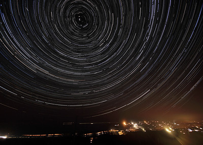 An image of Star Trails over Pembrokeshire. This image comprises around 4 hours and 20 minutes of images, showing how much the earth moves around the Pole Star ( in the centre of the circle) in that time.