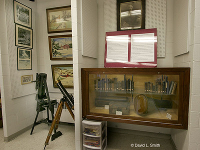 Case includes many books and instruments by Brashear. More of his telescopes appear on the left.