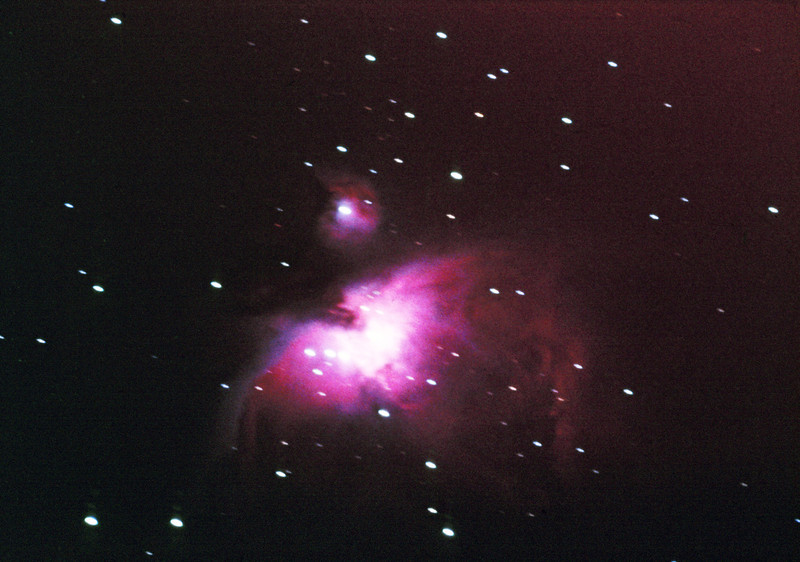 "Messier M42 NGC1976 Orion Nebula - January? 1980<br /> <br /> 12.5"" f/7.5 Calver Newtonian telescope with Olympus OM10 35mm film SLR at prime focus. 300 Sec exposure. Tracking errors evident.<br /> Kodak Ektachrome 400 Tranparencies. Scanned using Canon MP980 MFP 16/10/2011. Post processed by Adobe Photoshop CS5"