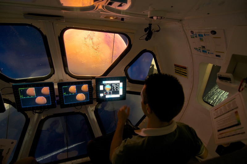 Simulation of commanding a spacecraft on the moon of Phobos with Mars out the viewport.