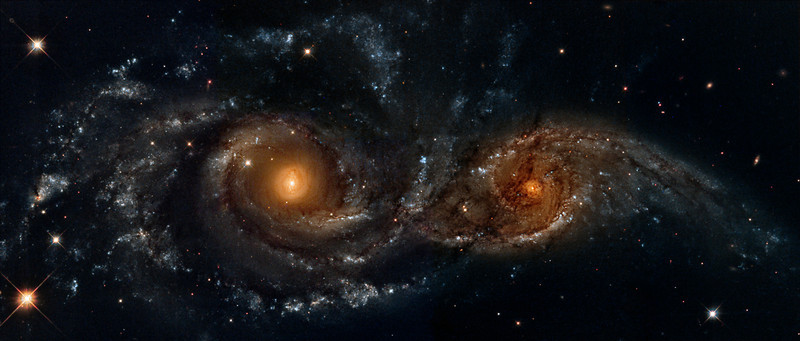 NGC2207 and IC2163 interacting galaxies....Hubble Space Telescope data from the Hubble Legacy Archive - a mosaic processed by Lynn Hilborn, April 10,2013.<br /> <br /> In the direction of the constellation Canis Major, two spiral galaxies pass by each other like majestic ships in the night. The near-collision has been caught in images taken by NASA's Hubble Space Telescope and its Wide Field Planetary Camera 2.<br /> <br /> The larger and more massive galaxy is cataloged as NGC 2207 (on the left in the Hubble Heritage image), and the smaller one on the right is IC 2163. Strong tidal forces from NGC 2207 have distorted the shape of IC 2163, flinging out stars and gas into long streamers stretching out a hundred thousand light-years toward the right-hand edge of the image.<br /> <br />  The calculations indicate that IC 2163 is swinging past NGC 2207 in a counterclockwise direction, having made its closest approach 40 million years ago. However, IC 2163 does not have sufficient energy to escape from the gravitational pull of NGC 2207, and is destined to be pulled back and swing past the larger galaxy again in the future.<br /> <br /> The high resolution of the Hubble telescope image reveals dust lanes in the spiral arms of NGC 2207, clearly silhouetted against IC 2163, which is in the background. Hubble also reveals a series of parallel dust filaments extending like fine brush strokes along the tidally stretched material on the right-hand side. The large concentrations of gas and dust in both galaxies may well erupt into regions of active star formation in the near future.<br /> <br /> Trapped in their mutual orbit around each other, these two galaxies will continue to distort and disrupt each other. Eventually, billions of years from now, they will merge into a single, more massive galaxy. It is believed that many present-day galaxies, including the Milky Way, were assembled from a similar process of coalescence of smaller galaxies occurring over billions of years.  Text from NASA. Data from the Hubble Legacy Archive established by the Space Telescope Science Institute, the Space Telescope European Coordinating Facility and the Canadian Astronomy Data Centre.