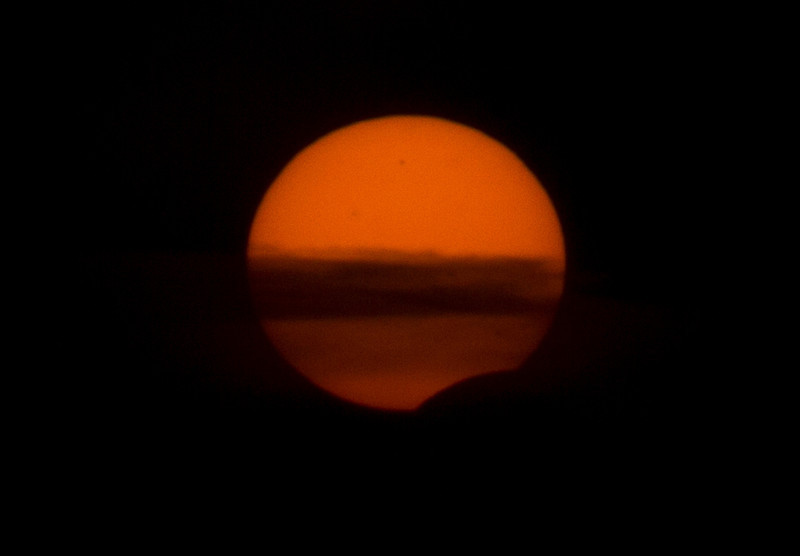 May 20 2012 Solar Eclipse as seen from north of Cobourg at sunset. This is just before sunset, passing through a cloud layer with the Moon blocking the bottom of the sun. The full eclipse was seen in the southwest USA. Photo by Lynn Hilborn with Canon 60D and 200mm lens with solar filter