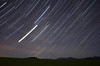 Star trails and airplanes over Whiteface Mountain and moonlit field