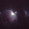 Messier M42 NGC1976 Orion Nebula - 3/1/2011 (Processed and cropped stack)<br /> <br />  The 'Great Orion Nebula' is located in the sword of Orion and is one of the brightest nebula in the sky, and perhaps the best known. It is a young star formation region with very hot high-UV stars ionising and 'lighting' the nebula.The brightness of these young stars make this an astrophotography challenge as the central regions are very bright in comparison to the tenous outer nebula and over exposure becomes a problem. High Dynamic Range (HDR) techniques must be used to produce an image with a 'flattened' brightness range, more akin to the way the human eye perceives a wide range of brightness.<br /> <br />  To the northeast (right as shown) of the Orion Nebula is the 'Running Man Nebula' a blue reflection nebula, caused by reflected light on a dark non-ionised region of nebulosity.<br />  <br /> HDR initial attempt, done in mid-2011, using DeepSkyStacker 3.3.2 Stacking 80% of:<br />  12 Images ISO 800, 15 Sec, 6 DARK, 0 BIAS, 0 FLATS (see also separate stack)<br />  6 Images ISO 800, 30 Sec, 32 DARK, 0 BIAS, 0 FLATS (see also separate stack)<br />  20 Images ISO 800, 120 Sec, 11 DARK, 0 BIAS, 0 FLATS (see also separate stack)<br />  Post processed with Adobe Photoshop CS4.<br /> <br /> I failed to get the colour balance right here and pushed to far into the blue, which highlights the Running Man, but at the expense of reds in the Orion nebula. See my re-processed attempt in this gallery.<br /> <br /> Telescope - Apogee OrthoStar LOMO 80/480 with Hotech SCA T-Adapter, Hutech IDAS LPS-P2 filter, Canon 400D DSLR, Ambient xxC (not recorded). Mount - Skywatcher NEQ6 Pro. Guidescope - Orion ShortTube 80 with Star Shoot Auto Guider.
