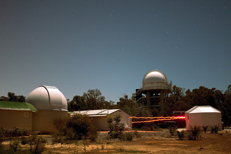 Perth Observatory Domes under Moonlight with a red headlight roaming through the scene