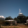 Perth Observatory Domes under Moonlight with large plane banking