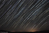 Startrails with 182 pics taken from 9:30pm-10:50pm Sunday Aug.11, 2013. Big fireball in center and smaller meteor at bottom. This was taken facing east and notice how the circles are curving one way at top left and other way at lower right. Split on northern and southern hemisphere stars.