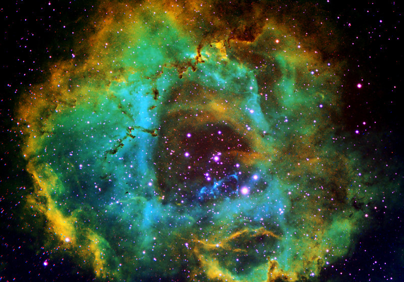 NGC 2237 - Rosette Nebula|<br /> The Rosette Nebula is a large, circular H II region located near one end of a giant molecular cloud in the Monoceros region of the Milky Way Galaxy. The open cluster NGC 2244 is closely associated with the nebulosity, the stars of the cluster having been formed from the nebula's matter.The cluster and nebula lie at a distance of some 5,200 light years from Earth (although estimates of the distance vary considerably) and measure roughly 130 light years in diameter. The radiation from the young stars excite the atoms in the nebula, causing them to emit radiation themselves producing the emission nebula we see.<br /> **********************************************************************************************<br /> Processed using Hubble Palette Sii=red Ha=Green Oiii=Blue|<br /> This is work in progress, need to capature more data and this image had to be cropped due to miss framing during capture. JUST A DIFFERENT COLOR SCHEME MORE TRADATIONAL HUBBLE PALETTE<br /> ************************************************************************************************<br /> Captured using:<br /> Date: Over 3 nights 10-12th November 2009<br /> Site: My Backyard - Toongabbie NSW (suburb of Sydney Australia|<br /> Camera: QHY9 CCD (mono KAF 8300 chip) as main and QHY5 as guide|<br /> Filters: Sii 8nm (11x20min Bin2), Ha 7nm (7x20min)|, Oiii 8.5nm (11x20min Bin2)|<br /> MPCC Field Flattener<br /> Captured using Nebulosity 2 and PHD for guiding|<br /> Scope: WO FLT110 f/7 TMB|<br /> Guide Scope: SW 80mmx400mm|<br /> Mount: HEQ5 Pro|<br /> QHY Filter Wheel 2"