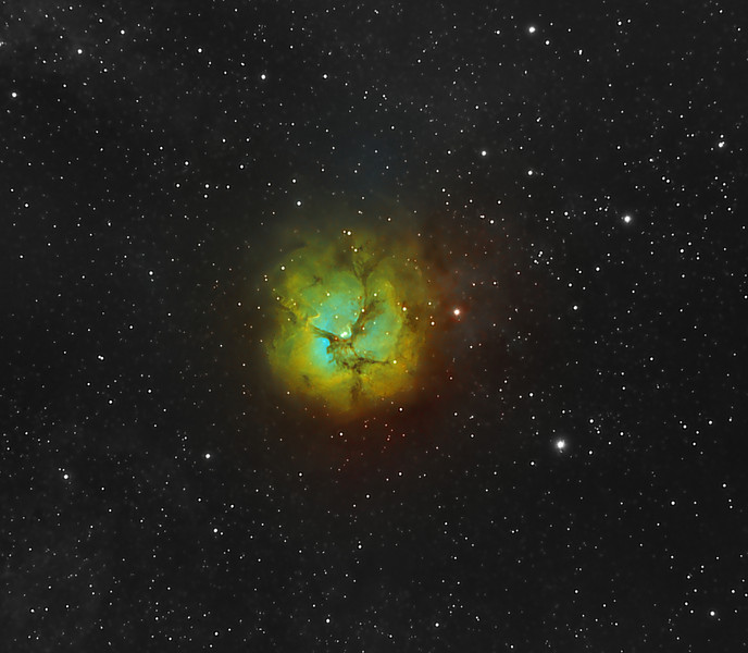 The Trifid Nebula (catalogued as Messier 20 or M20 and as NGC 6514) is an H II region located in Sagittarius. Its name means 'divided into three lobes'. The object is an unusual combination of an open cluster of stars, an emission nebula (the lower, red portion), a reflection nebula (the upper, blue portion) and a dark nebula (the apparent 'gaps' within the emission nebula that cause the trifid appearance, it is around 2000-9000 light years away and about 16 light years in diameter.<br /> **********************************************************************************************<br /> Processed using HST palette Red=Sii Green=Ha Blue=Oiii.<br /> **************************************************************************<br /> Captured using:<br /> Camera: QHY9 CCD (mono KAF 8300 chip) as main and QHY5 as guide|<br /> Filters: SII 8nm (3x25min), Ha 7nm (3x20min), OIII 8.5nm (9x20min)|<br /> Captured using Nebulosity 2 and PHD for guiding|<br /> Scope: WO FLT-110 Triplet f/7|<br /> Mount: HEQ5 Pro|<br /> QHY Filter Wheel 2"