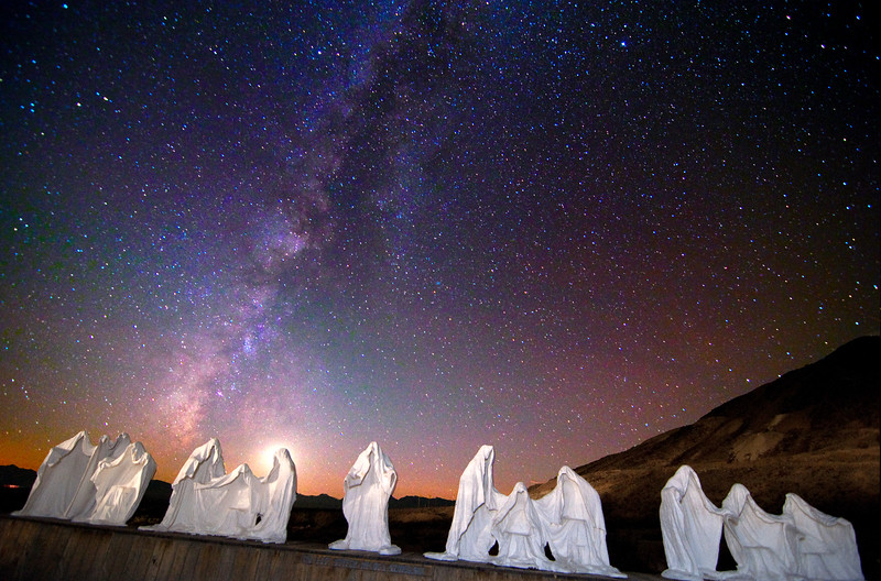 A sculpture of The Last Supper by Szukashi in the ghost town of Rhyolite, on the edge of Death Valley, at night.  The moon is setting behind the head of one desciple.