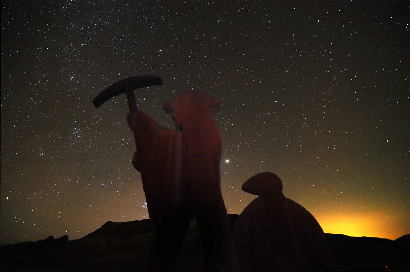 Sihouette of The Old Prospector sculpture in the ghost town of Rhyolite, on the edge of Death Valley.  The light from Beatty, NV is visible on the right.
