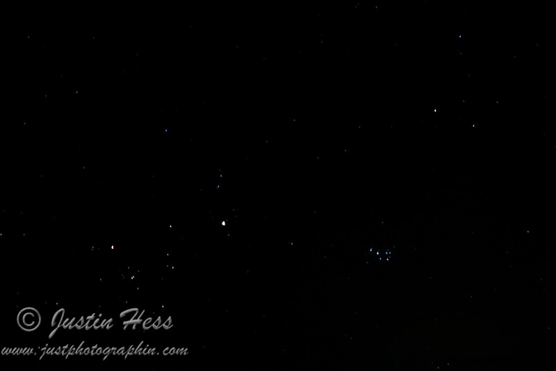 Part of Taurus on the left; Jupiter is the largest bright dot near the center of the picture; Pleiades, lower right, is pointing at Jupiter to the left.  So, Jupiter is between Taurus and Pleiades.