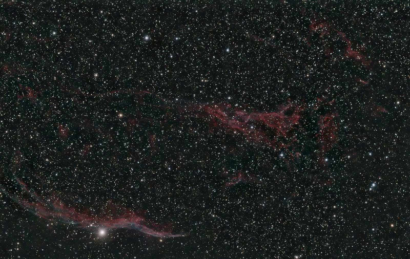 Target:  NGC 6960 (Western Veil Nebula, supernova remnent in Cygnus)<br /> <br /> Distance from Earth:  1500 light-years<br /> <br /> Image FOV:  139 x 88 arcmin<br /> <br /> Date/Time: 10/06/07 2150 EDT to 10/07/07 0145 EDT and 10/28/07 2010 EDT to 2330<br /> <br /> Mount: Takahashi NJP Temma II<br /> <br /> Telescope: Takahashi FS-78 refractor with Hutech 0.85x reducer/flattener (f/6.9) and Hutech LPS filter on 10/06/07 and Astronomik 13nm Ha filter on 10/28/07<br /> <br /> Camera: Starlight Xpress SXVF-M25C guided by Takahashi FS-60C with SBIG STV (f/5.9)<br /> <br /> Focus: Finger Lakes Instrumentation DF-2 with FocusMax/MaxIm DL software<br /> <br /> Sky conditions 10/06/07: transparency 3/5, seeing 4/5<br /> <br /> Sky conditions 10/28/07: transparency 4/5, seeing 2/5<br /> <br /> Moon:  Moonrise 10/07/07 0348 EDT; Moonrise 10/28/07 1958 EDT<br /> <br /> Images: Captured with MaxIm DL 4.60 at an image scale of 2.99 arcsec/pixel; On 10/06/07, 18 light exposures, 600 sec duration and no darks, 18 frames were used for alignment and stacking; on 10/28/07, 12, 900 sec lights and 1, 900 sec dark, 12 frames used for processing<br /> <br /> Processing: ImagesPlus 3 beta 9 &10 , RegiStar 1.0 and Photoshop CS3 with GradientXTerminator and Noise Ninja, image cropped, luminance data from Ha and red data from LPS image blended in PS and combined with blue and green data from LPS image, image cropped and downsampled
