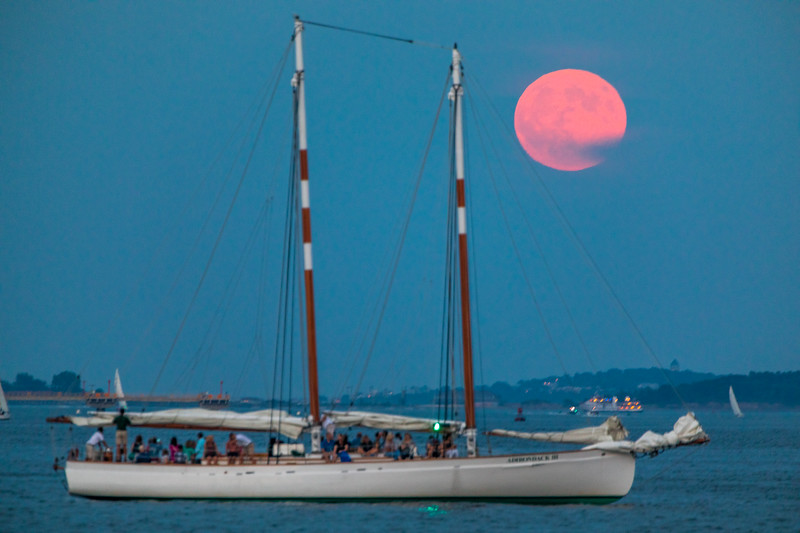 The Classic Harbor Line Boston Schooner Adirondack III cruising through the Harbor with the Full Buck Moon rising in the distance.