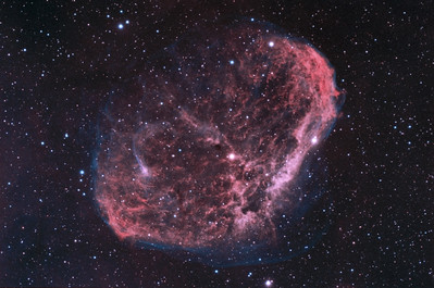 "Crescent Nebula (also known as NGC 6888, Caldwell 27, Sharpless 105) is an emission nebula in the constellation Cygnus, about 5000 light years away. It is formed by the fast stellar wind from the Wolf-Rayet star WR 136 (HD 192163) colliding with and energizing the slower moving wind ejected by the star when it became a red giant around 250,000to 400,000 years ago. The result of the collision is a shell and two shock waves, one moving outward and one moving inward. The inward moving shock wave heats the stellar wind to X-ray-emitting temperatures. [Description from wikipedia]   Ha: 20 x 30m (5nm)  OIII: 16 x 30m (3nm) total exposure time: 18 hours.   Main Camera: QSI 583 WSG Guide Camera: SXV Lodestar (on OAG) Mount: Astro-Physics Mach 1 Scope: Celestron Edge HD 8"" (FL: 2032mm) Adaptive Optics Unit: SXV-AO-LF Image Aquisition software MaximDL Registed, Calibrated and Stacked in MaximDL Post Processed with PixInsight 1.8 and Photoshop CS6"