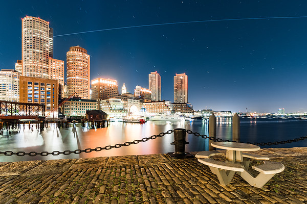 The Int'l Space Station emerging from shadow behind One International Place and flying over the Financial District skyline as viewed from Fan Pier Park in the Boston Seaport District.