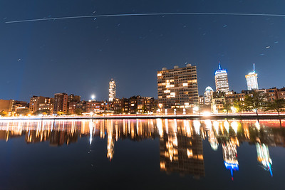 The Back Bay skyline in Boston, reflected off the Charles River Esplenade Lagoon while the Int'l Space Station flies overhead.