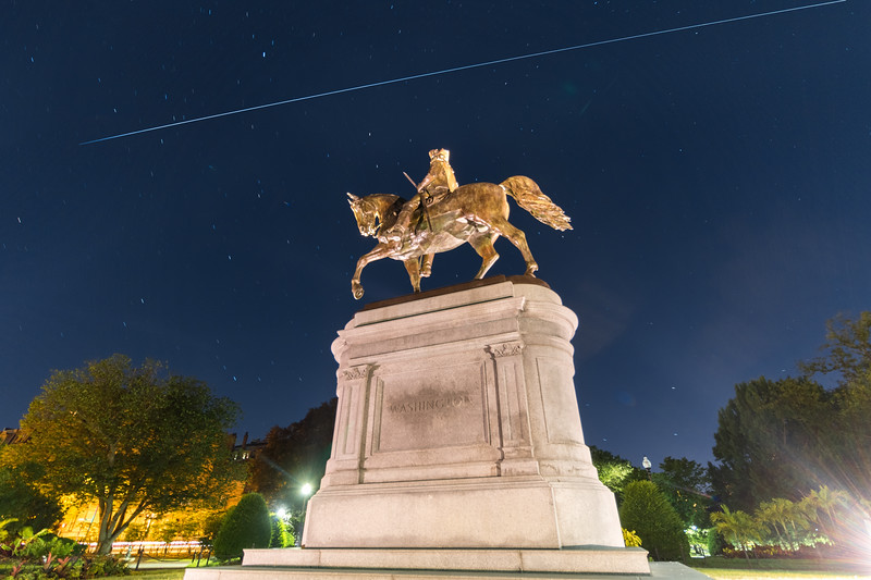 The International Space Station flying high over the George Washington statue in the Boston Public Garden.