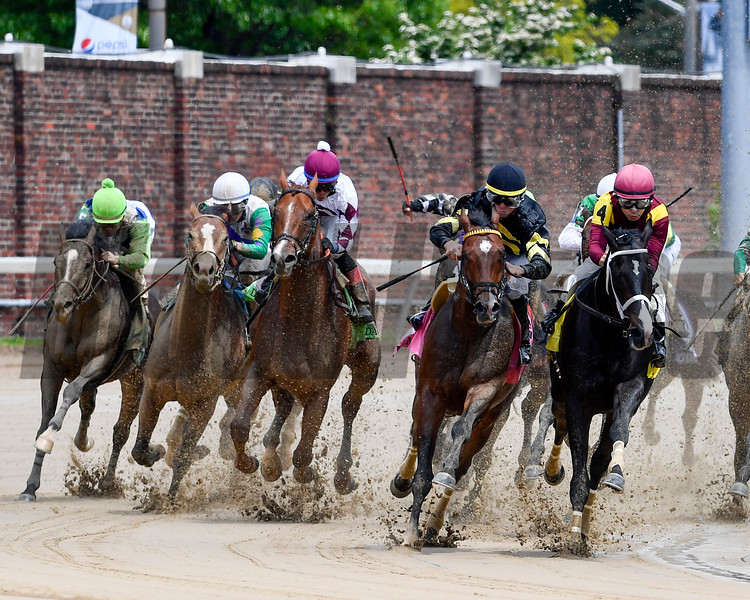 Wild Shot (black cap, yellow band), with Corey Lanerie aboard, leads the field around the final turn in the 93rd running of The Pat Day Mile (G3).