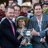 Ron Winchell, right owner of Gun Runner receives the winner's trophy from Mary Lou Whitney with an assist from Chris Kay, CEO of NYRA in the winner's circle after the 90th running of The Whitney Stakes at the Saratoga Race Course  Saturday Aug. 5, 2017 in Saratoga Springs, N.Y.  (Skip Dickstein