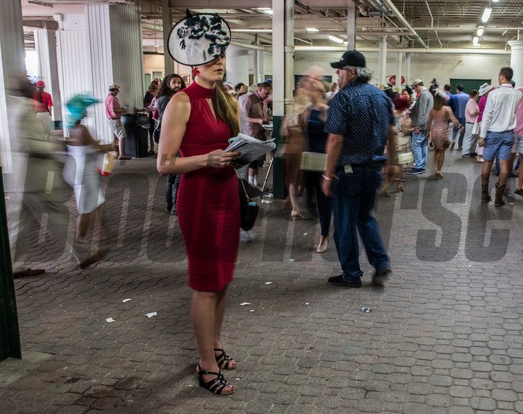 A lady in red checks the race card on Oaks Day at Churchill Downs Friday May 4, 2018 in Louisville, Kentucky.  Photo by Skip Dickstein