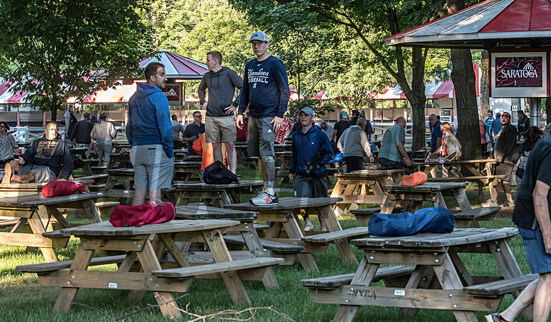 Hundreds of racing patrons stake their claim to a picnic table for Opening day at the Saratoga Race Course Friday July 20, 2018 in Saratoga Springs, N.Y.  (Skip Dickstein)