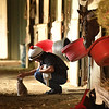 Barn foreman and exercise rider David Meah pets a cat at the barn of Richard Baltas at Santa Anita. Photo: Wally Skalij
