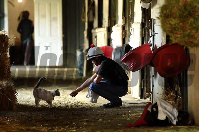 Barn foreman and exercise rider David Meah pets a cat at the barn of Richard Baltas at Santa Anita. Photo: Wally Skalij