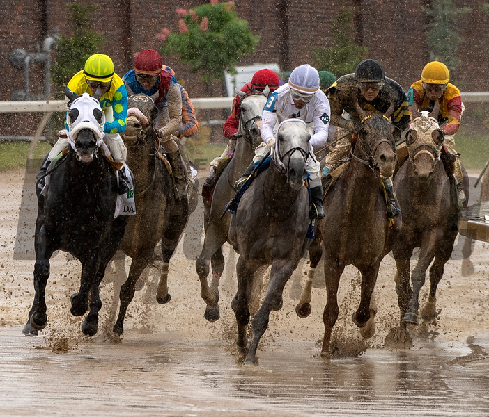 A rainy finish for Funny Duck (black cap, right) for the Pat Day Mile.