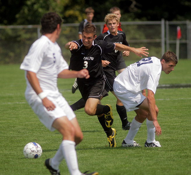 By Alex Turco--  Junior defender Josh Schlake shoves defenders while taking the ball downfield during DePauw's game against Elmhurst, Saturday, Sept. 5, 2009. DePauw won a shut-out 2-0 victory.