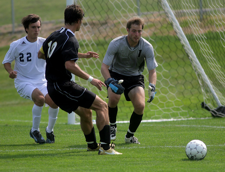 By Alex Turco--  Senior goalie Ted Jacobi dives for a ball while senior back Beau Sorg assists during DePauw's game against Elmhurst, Saturday, Sept. 5, 2009. DePauw won a shut-out 2-0 victory.