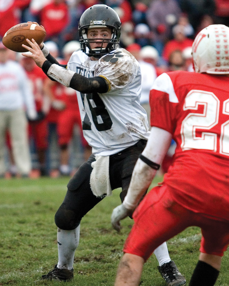 Freshman quarterback Spud Dick throws the ball as Wabash defenders advance on him. <br /> <br /> Photo by Alex Turco
