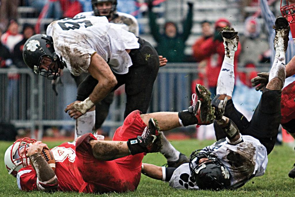 Senior defensive lineman Dustin Hertel crashes onto a Wabash player. <br /> <br /> Photo by Alex Turco