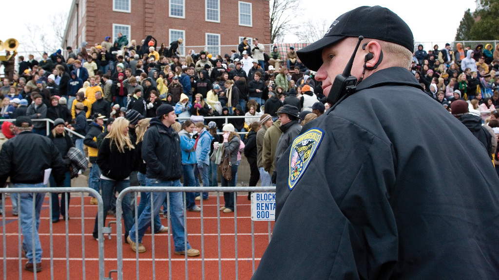 A Crawfordsville police officer keeps a close watch on Depauw fans during the game.  <br /> <br /> Photo by Alex Turco
