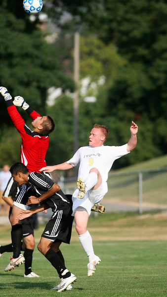 Senior forward Mike Harris fights the goalie for the ball  during DePauw's game against Holy Cross. The Tigers won 2-0 in the game August 29, 2008, at Bowman Field.   Photo by Alex Turco