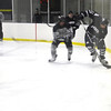 Michael Lata '14 slides along the boards with the puck.