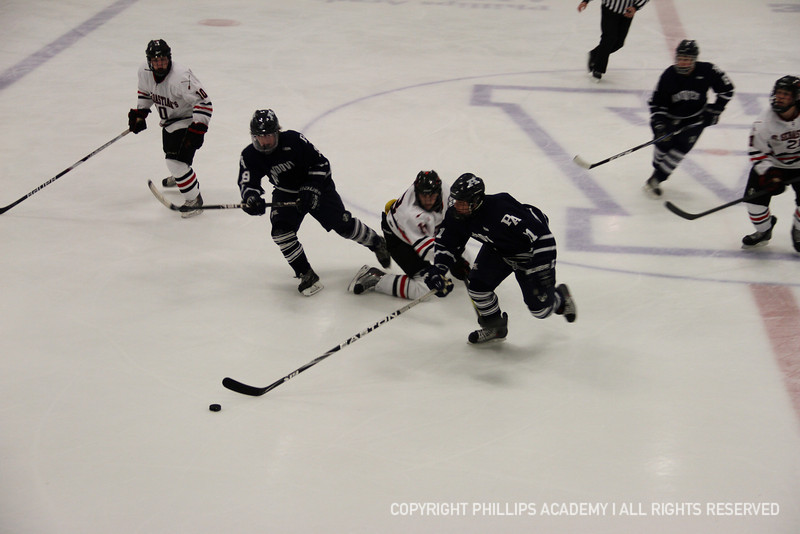 Michael Lata '14 sweeps the puck past a St. Seb's opponent.