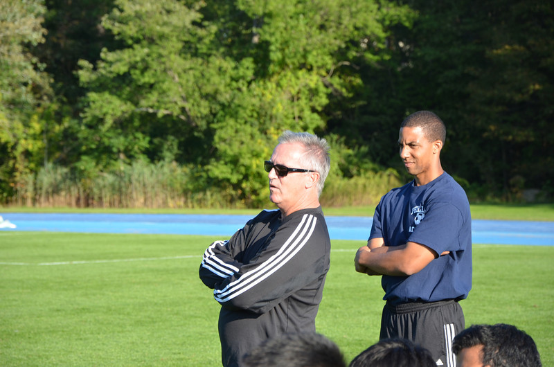Head coach Bill Scott and assistant coach Joe Yonga intensely watch their team play.