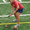Coach Martha Fenton demonstrates a proper pass to her varsity field hockey players.
