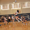 Andover caught in mid air as they spike the ball over the net.