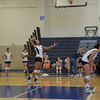 The girls in blue strike the ball for a great serve.