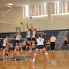 The big blue jumps to deflect the ball from coming over the net.