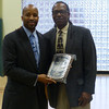 MassBay Associate Director of Athletics, Recreation and Wellness, Khari Roulhac receives a plaque from Director Bill Raynor.