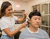 Megan Pigott, a stylist at LM Studio, demonstrates using a comb as a guide for clippers on her fiancée Jason Chong during the covid-19 pandemic at LM Studio on Wednesday, April 15, 2020.  LM Studio is in the Sola Salon Studios in Alpharetta and suggestions for men include getting good mirror views and making small adjustments, holding down the ear and using a comb with clippers.  (Jenni Girtman for Atlanta Journal Constitution)