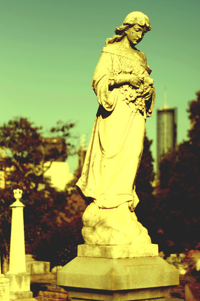 Atlanta, GA: Funerary statue in Oakland Memorial Cemetery with the Westin building in the background.