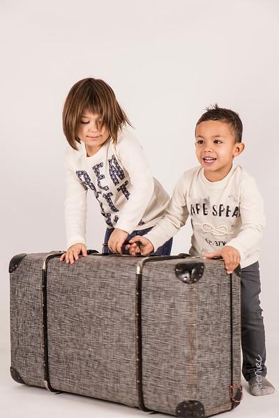 Niños levantan una maleta. Reportajes de fotografía infantil para ver crecer la familia. fotografo infantil, fotografo familia, fotografo de navidad, elena rubio fotografa mollet para elenircfotografia , fotografa infantil barcelona 1