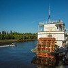 A river boat passes by the Riverboat Discovery at dock at Steamboat Landing, Fairbanks.